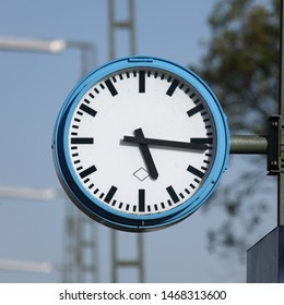 Typical platform clock in German train stations. Black fingers and numbers on white clock face. Blue case. Time on clock: 05h16