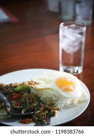 typical popular fast food THAI lunch menu everywhere, rice with fried chicken or pork with garlic fish sauce and pepper authentic street food shot on textured wooden school canteen table top