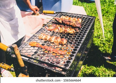 Typical popular street barbecue from Brazil called Espetinho de Carne. Meat pieces on a skewer, roasting on a portable grill, outdoors.