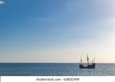 Typical portuguese caravela made of wood in the ocean during sunset