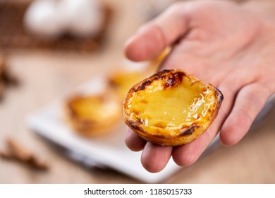 """Typical Portuguese custard pies - """"Pastel de Nata"""" or """"Pastel de Belem"""". traditional portuguese pastry. holding by a chef."""