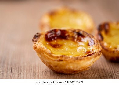 "Typical Portuguese custard pies - ""Pastel de Nata"" or ""Pastel de Belem"". traditional portuguese pastry. On a wooden table."