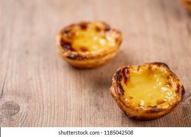 """Typical Portuguese custard pies - """"Pastel de Nata"""" or """"Pastel de Belem"""". traditional portuguese pastry. On a wooden table."""