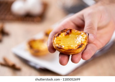 "Typical Portuguese custard pies - ""Pastel de Nata"" or ""Pastel de Belem"". traditional portuguese pastry. holding by a chef."