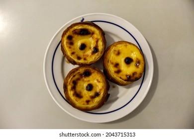 Typical Portuguese custard pies, Pastel de Nata or Pastel de Belem. A close-up of traditional Portuguese custard pastries in traditionl caffe - restorant. Pastel de nata. Pastéis de Belém.