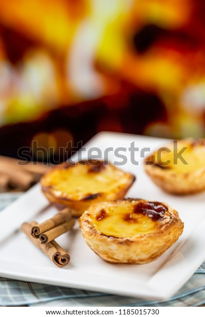 """Typical Portuguese custard pies - """"Pastel de Nata"""" or """"Pastel de Belem"""". traditional portuguese pastry. in front of a fire oven."""