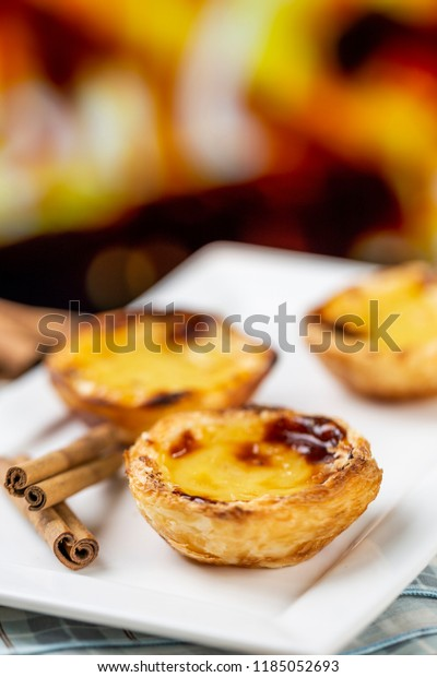 "Typical Portuguese custard pies - ""Pastel de Nata"" or ""Pastel de Belem"". traditional portuguese pastry. in front of a fire oven."