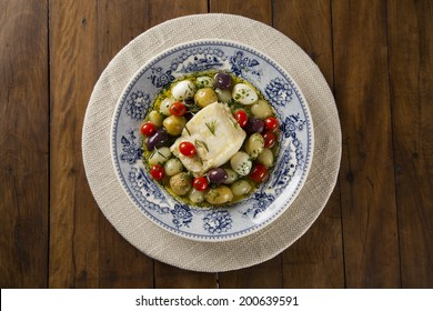 A typical Portuguese dish with codfish called Bacalhau do Porto in a original portuguese plate seen from above