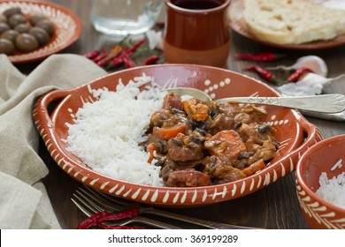 typical portuguese dish feijoada with rice in ceramic bowl and red wine on brown background