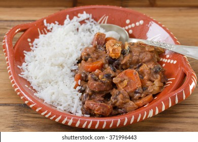typical portuguese dish feijoada with rice in ceramic bowl on brown wooden background