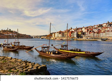 "Typical portuguese wooden boats, called ""barcos rabelos"" transporting wine barrels on the river Douro with view on Villa Nova de Gaia  in Porto, Portugal"