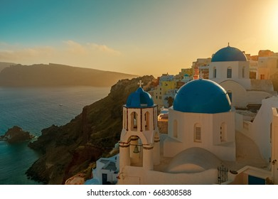 Typical postcard shot of Greek houses and blue dome churches by sunset in the island of Santorini