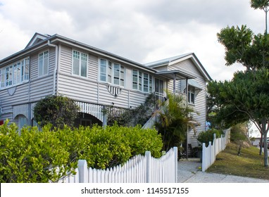 Typical Queensland house with tropical foliage and white picket fence on overcast day in Australia