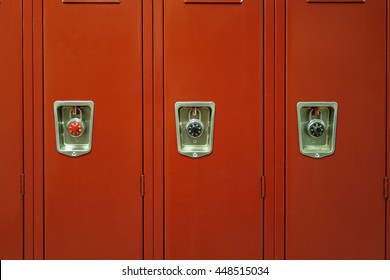 Typical red, American high school lockers with locks on them.
