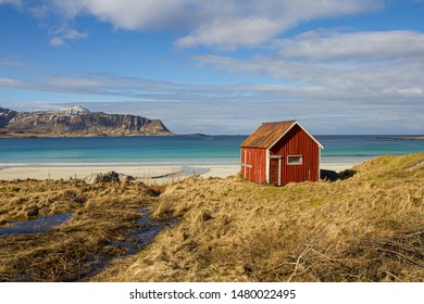 A typical red nordic hut at the seaside. Amazing and beautiful sunlit beach with mountain range in the background.