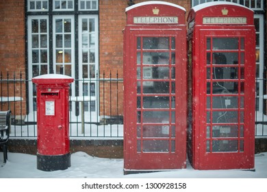 typical red post box and telephone kiosk on UK street during blizzard with snow on top