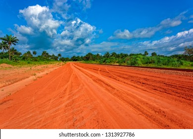 Typical red soils unpaved rough countryside road along railway track in Guinea, West Africa.