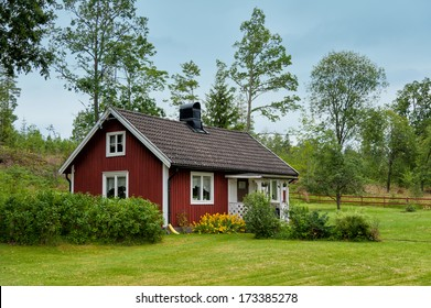 Typical red wooden cottage in the countryside near Hoegsby, Sweden