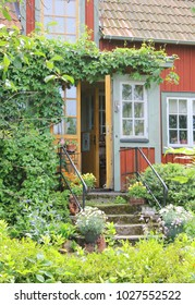 Typical red wooden cottage entrance on the countryside of Sweden, surrounded by beautiful greenery at summer time.