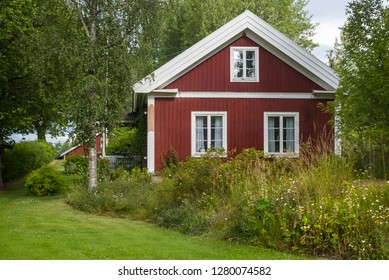 Typical red wooden house in Sweden with white frames around the windows, blooming wild flowers in front of the house and green meadow.