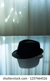Typical retro style spy detective novel scene of  trilby hat on glass coffee table in hotel room.