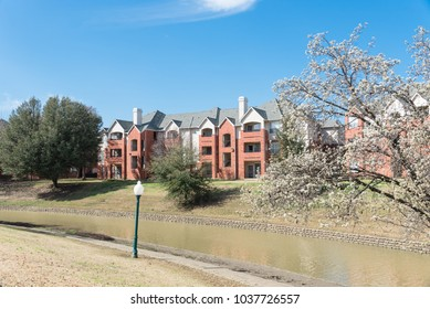 Typical riverside apartment building complex at springtime in Irving, Texas, USA. Cloud blue sky and blossom tree.