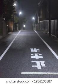 """Route typique de nuit avec le panneau """"stop"""" en japonais écrit au sol."""
