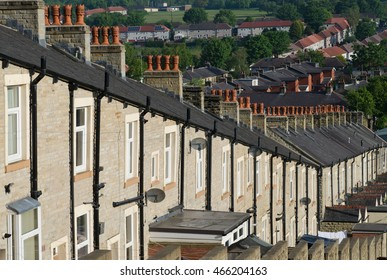A typical row of Lancashire town stone facade built and slate roof covered terraced houses. Red chimney stacks top the buildings with the hills visible in the distance - Taken early morning.