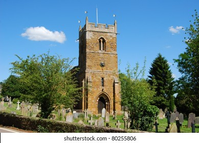 Typical rural English village church and cemetery in Northamptonshire, Great Britain, horizontal image with blue sky and clouds
