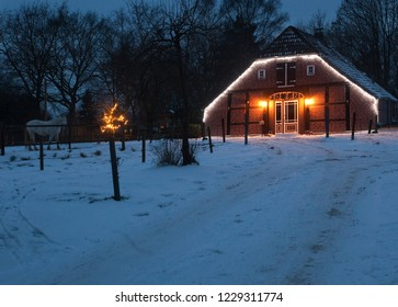 typical rural northern german house in framework style decorated with christmas lights at beautiful scenic dawn with snow, a horse can be seen on a meadow in background
