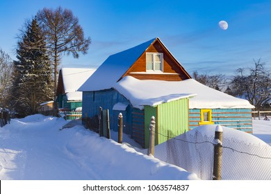 Typical Russian dacha, blue sky with  Moon. Cabins painted with vivid colors look great surrounded with snow