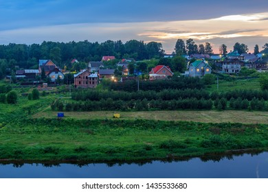 Typical Russian village on banks of Volga River with modern cottage houses. Sunset over forest. Suburb of Rzhev, Tver Region, Russia. ancient Russian city of Rzhev, located on Volga river.