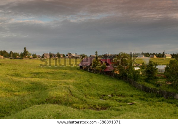 a typical Russian village, wooden houses, the smoke from the chimney, blue sky, green fields
