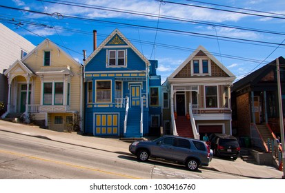 Typical San Francisco residential steep street with row of wooden victorian houses in pastel colors near Alamo Square. Car parked in the street. SAN FRANCISCO USA - OCTOBER 15, 2012