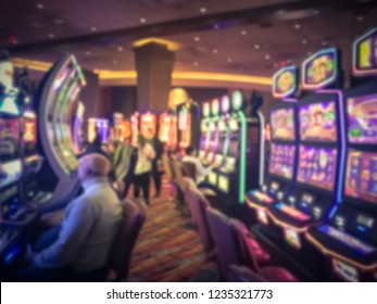 Typical scene of players with slot machine at casino in America. Defocused gambling abstract background