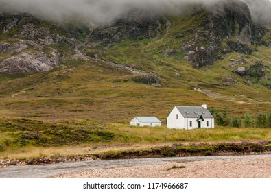 Typical Scottish white farmhouse used as a guesthouse or hostel under the mountains in Glencoe area in the Highlands of  Scotland UK