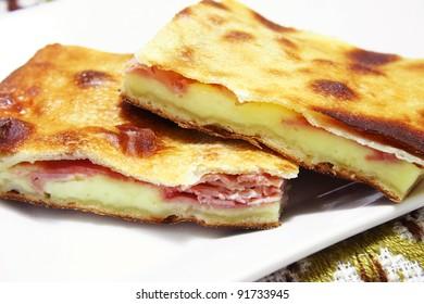 Typical Sicilian flat sfoglia pizza, filled with ham and mozzarella cheese
