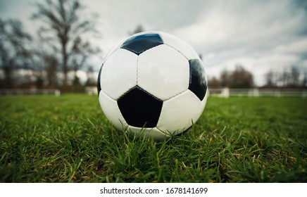 Typical soccer ball on the free kick marking line, outdoors on the stadium field. Traditional football ball on the green grass turf before goal. Spring sports leisure and healthy activity.
