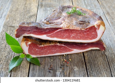 Typical South Tyrolean bacon divided into two halfes lying on a rustic table