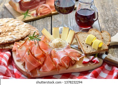 Typical South Tyrolean snack with bacon, horseradish, mountain cheese and farmhouse bread, served with local red wine