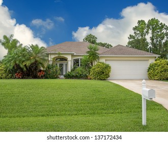 Typical Southwest Florida concrete block and stucco home in the countryside with palm trees, tropical plants and flowers, a bahia grass lawn and pine trees.