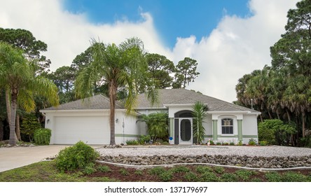 Typical Southwest Florida concrete block and stucco home in the countryside with palm trees, tropical plants and flowers and pine trees.