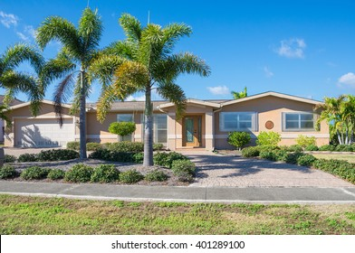 Typical Southwest Florida Concrete Block and Stucco Home.  Clear hurricane shutters on the windows and palm trees in the landscape.