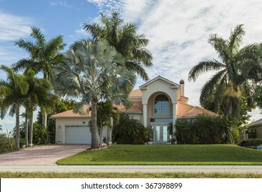 Typical Southwest Florida home in the countryside with palm trees, tropical plants and flowers, grass and pine trees. Inlaid pavement at the entrance. Florida