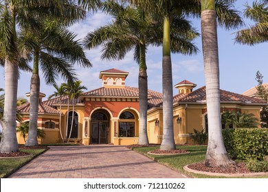 Typical Southwest Florida luxury concrete block and stucco home in the countryside with palm trees, tropical plants and flowers, grass lawn and pine trees. Florida. South Florida single family house