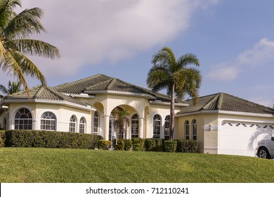 Typical Southwest Florida white concrete block and stucco home in the countryside with palm trees, tropical plants and flowers, grass lawn and pine trees. Florida. South Florida single family house