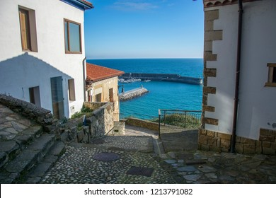 Typical Spanish alleyway with sea, blue sky and cold colours