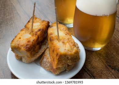 Typical spanish appetizer called pincho de tortilla de patatas. Delicious Spanish omelette with two glasses of draft beer