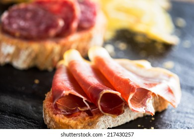 """Typical spanish appetizer called """"pinchos"""" with spanish ham and slice of bread."""