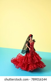 a typical spanish doll dressed as a flamenco dancer, with the characteristic traje de flamenca, the typical dot-patterned dress, in a yellow and blue background with a blank space on top
